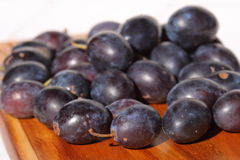 Damsons on wooden chopping board B Stock Photos