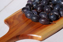 Damsons on wooden chopping board A Royalty Free Stock Photos