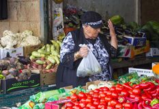 Damstallhållare med hennes lyftta hand, som hon fyller en plastpåse med nya grönsaker på den Mahane Yehuda marknaden i J fotografering för bildbyråer