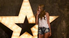Damstjärna elegant flicka som lyssnar till musik på lager videofilmer