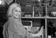 Damy blondynka w szkockiej kracie odziewa brać książkę od półka na książki Domowej biblioteki pojęcie Dziewczyna patrzeje dla ksi obrazy stock