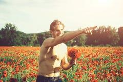 damy ` mężczyzna mięśniowy mężczyzna w polu czerwony makowy ziarno Zdjęcie Royalty Free