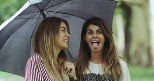 Damy na podeszczowym dniu pod parasolowy patrzeć prosto kamera i robić śmiesznym twarzom zbiory