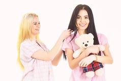 Damy na uśmiechać się twarze z mokiet zabawki niedźwiedziem patrzeją ślicznymi Dziewczęcy czasu wolnego pojęcie Siostry, najlepsi obrazy stock
