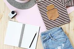 Damy ` s strój z cajgami zwiera, pusty notatnika papier i akci kamera na drewnianym tle Fotografia Royalty Free