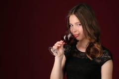 Damy wzruszający wineglass jej wargami z bliska tło ciemnoczerwony Fotografia Stock
