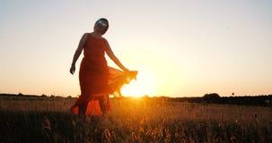 Dança à moda feliz da mulher e gerencio em um grande campo no por do sol fotografia de stock