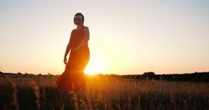 Dança à moda feliz da mulher e gerencio em um grande campo no por do sol no slo-mo video estoque