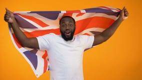 Dança afro-americana do homem com bandeira britânica, vencedor de apoio da eleição, político video estoque