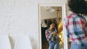 Dança afro-americano engraçada encaracolado da menina e canto com o secador de cabelo na frente do espelho em casa fotografia de stock royalty free