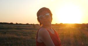 Dança animador da mulher com inspiração em um grande campo no por do sol no movimento lento filme