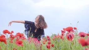 Dança bonita da jovem mulher em um campo da papoila que sorri felizmente Conex?o com a natureza Lazer na natureza florescer filme
