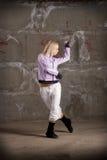Dança bonita da menina do lúpulo do quadril sobre a parede cinzenta Foto de Stock Royalty Free