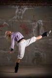 Dança bonita da menina do lúpulo do quadril sobre a parede cinzenta Imagens de Stock