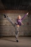 Dança bonita da menina do lúpulo do quadril sobre a parede cinzenta Imagem de Stock