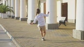 Dança bonita nova da menina no parque a menina dança e salta o passeio ao longo da estância turística tiro do steadicam 4K vídeos de arquivo