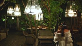 Dança bonita nova da mulher na noite em um café Lâmpadas brancas e mobília de madeira e de vime Relaxe e conceito despreocupado filme