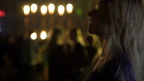 Dança bonita nova da mulher no clube noturno e apreciação do grupo do DJ, abrandamento filme