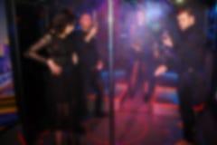 Dança borrada abstrata dos povos no partido no clube noturno imagem de stock