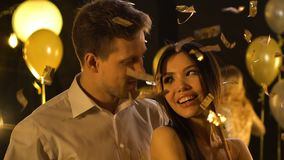 Dança caucasiano do homem com a mulher asiática bonita sob confetes de queda, partido vídeos de arquivo
