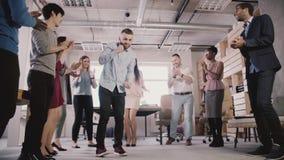 Dança caucasiano nova do empregado com os colegas, comemorando a realização do negócio no movimento lento ocasional de partido de filme