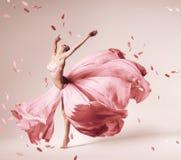 Dança da bailarina no vestido cor-de-rosa de fluxo com pétalas do voo imagem de stock royalty free