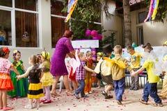 Dança da criança em idade pré-escolar em um círculo com o professor