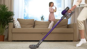 Dança da dona de casa com um aspirador de p30 na sala de visitas Sua filha pequena que salta no sofá Movimento lento video estoque