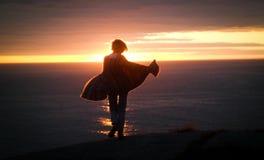 Dança da jovem mulher no oceano durante o por do sol Imagem de Stock