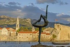 Dança da menina da escultura Contra o contexto da cidade velha de Budva fotografia de stock