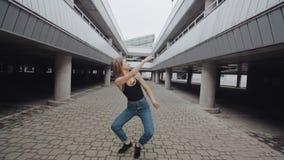 A dança da menina e executa a dança moderna da moda ou do hip-hop, estilo livre contemporâneo em urbano industrial video estoque
