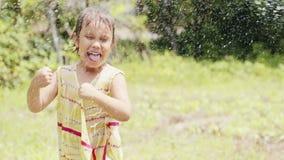 Dança da menina sob o pulverizador de uma mangueira de jardim video estoque