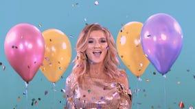 Dança da mulher em um partido em um vestido brilhante bonito Com balões e confitti vídeos de arquivo