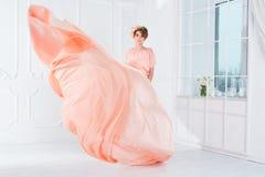 Dança da mulher gravida no voo cor-de-rosa do vestido de noite no vento Tela de ondulação, tiro da forma imagem de stock