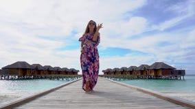 Dança da mulher na ponte na praia com água transparente do oceano em Maldivas vídeos de arquivo