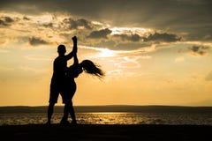 Dança da silhueta dos pares na praia Imagens de Stock