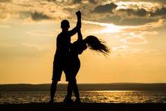 Dança da silhueta dos pares na praia Fotos de Stock Royalty Free