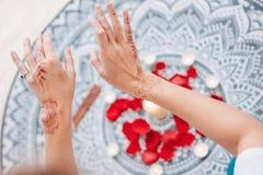 Dança das mãos fêmeas com o mehendi sobre o altar das velas e das pétalas de rosa, práticas das mulheres imagens de stock royalty free