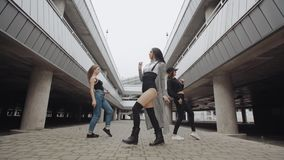 A dança das meninas, executa o hip-hop moderno ou a dança da moda no parque de estacionamento, levantando, estilo livre contempor filme