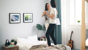 Dança de amor adorável dos pares na cama em casa que abraça tendo o divertimento filme