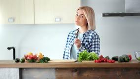 Dança de sorriso da mulher feliz bonita do vegetariano que come legumes frescos no tiro médio da cozinha video estoque