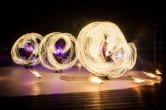 Dança de surpresa da mostra do fogo Dançarinos do fogo nos trajes bonitos que jogam com chama fotos de stock