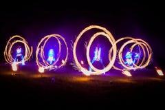 Dança de surpresa da mostra do fogo Dançarinos do fogo nos trajes bonitos que jogam com chama imagem de stock