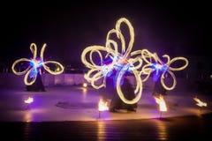 Dança de surpresa da mostra do fogo Dançarinos do fogo nos trajes bonitos que jogam com chamas coloridas imagens de stock