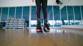 Dança desportiva da mulher com as sapatas do kangoo no gym filme