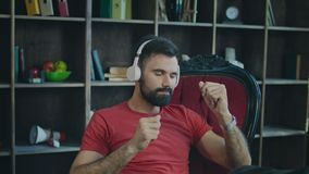 Dança do homem de negócio na cadeira Homem novo que escuta a música nos auscultadores vídeos de arquivo