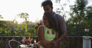 Dança dos pares no terraço do verão durante a ceia romântica, o homem atrativo e a mulher na data fora sobre a paisagem do por do video estoque