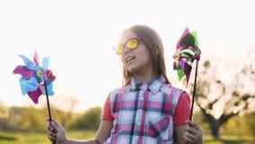 Dança engraçada da menina com um moinho de vento colorido do brinquedo vídeos de arquivo