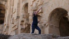 Dança engraçada do adolescente feliz da menina em paredes rochosos do fundo video estoque