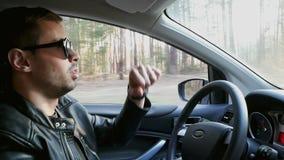 Dança engraçada do homem no carro ao conduzir no movimento lento filme